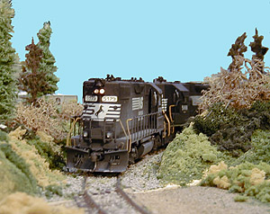Tom Gaines' highly-detailed NS GP-38s lead a string of covered hoppers along the branch line to a large grain elevator.