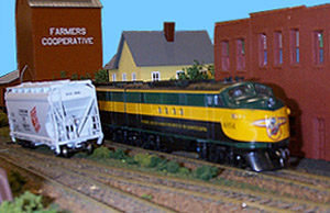 A C&amp;NW FT crawls past a bad-ordered hopper that has developed<br>a severe list on one of Jeff Fryman's Branchton modules.<br>