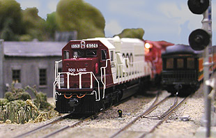 A westbound Soo Line freight roars through Mud Creek just moments after<br>  an eastbound Great Northern passenger extra clears the road crossing.