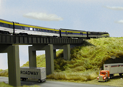 C&amp;O passenger train #13 sweeps across a trestle high<br>over a highway on Brian Everett's corner module.