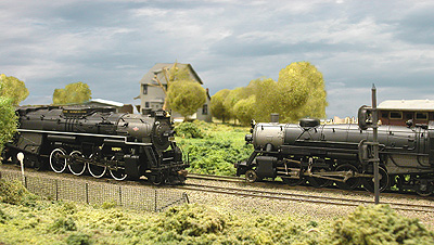Two steam locomotives meet on a sweeping curve.
