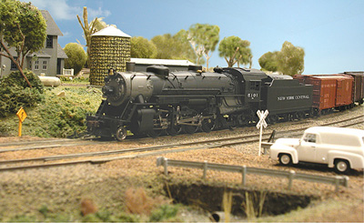 A New York Central freight approaches a rural grade crossing.