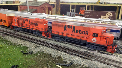 A pair of Ann Arbor GP35s lead a freight through a yard
