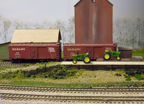 Tractors are being unloaded at the Rockfield team track, while<br/>boxcars wait to be loaded at the elevator behind it.