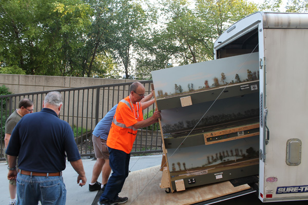 John Hartmann and Ross Kudlick (behind) unloading a rack of modules from a trailer<br/>at the top of the ramp at Kansas City.